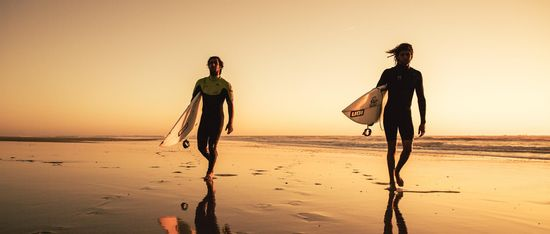 surfers on beach at sunset Portugal